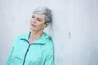 Smiling sporty mature woman with earbuds leaning against concrete wall - VWF00033