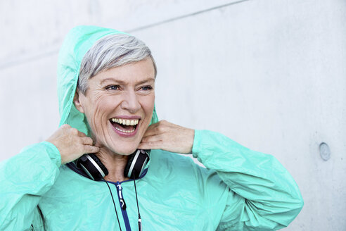 Portrait of laughing sporty mature woman with headphones - VWF00036