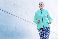 Smiling mature woman jogging along concrete wall - VWF00039