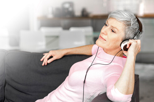 Portrait of mature woman sitting on couch listening music with headphones - VWF00042
