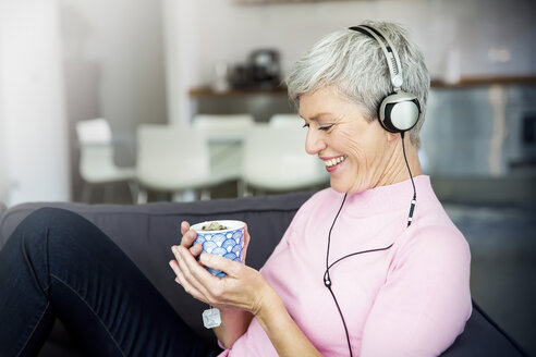 Laughing mature woman sitting on couch with cup of tea listening music with headphones - VWF00045