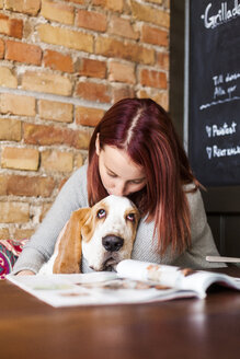 Young woman kissing Basset Hound at cafe table - ASTF00441