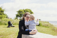 Happy mother with son on grassy field - ASTF00588