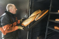 Side view of mature fisherman arranging chopped fish on shelf - ASTF00723