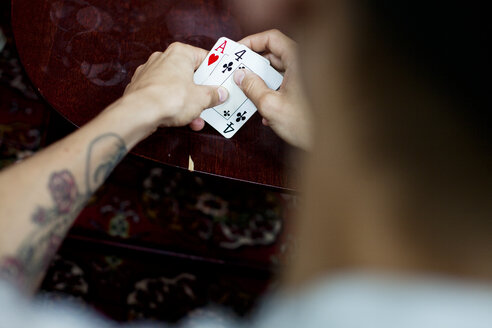 Cropped image of man playing cards at home - ASTF00783