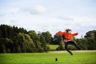 Happy young woman jumping on field - ASTF00873