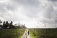 Rear view of man walking with dog on dirt road amidst farm against cloudy sky - ASTF00921