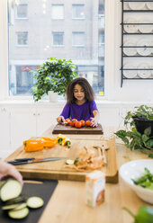 Girl chopping tomatoes in kitchen - ASTF00936