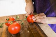 Cropped image of girl slicing tomatoes on cutting board in kitchen - ASTF00942