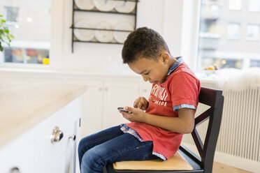 Boy playing games on mobile phone at home - ASTF00948