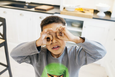 Portrait of boy looking through hands as binoculars at home - ASTF00966