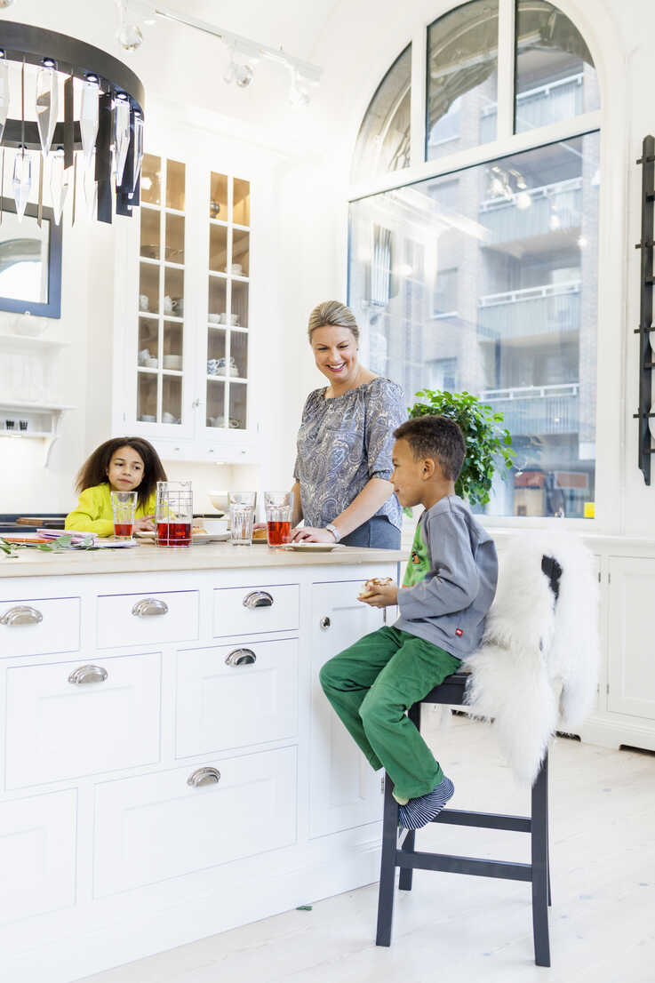 Happy mother with children having breakfast at kitchen island - ASTF00969 - Astrakan Images/Westend61