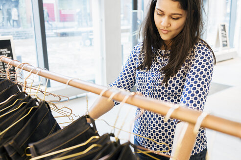 Confused woman choosing jeans in factory - ASTF00990