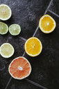 Directly above shot of sliced citrus fruits on tiled floor - ASTF01083