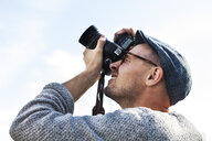 Low angle view of man photographing sky through digital camera - ASTF01188
