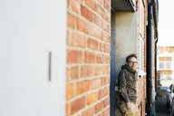 Portrait of carpenter leaning on brick wall - ASTF01245