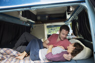 Affectionate couple cuddling in the back of camper van - HEROF03598