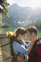 Affectionate couple hiking hugging at remote sunny mountain lakeside - HEROF03601