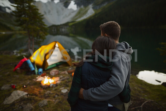 Affectionate couple cuddling near campfire at campsite - HEROF03604 - Hero Images/Westend61