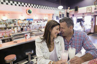 Affectionate mature couple enjoying milkshakes at soda fountain shop - HEROF03607
