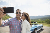 Affectionate couple taking selfie near convertible - HEROF03610
