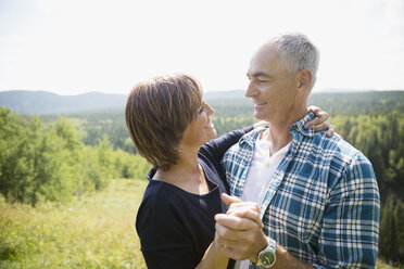 Affectionate mature couple hugging at sunny remote hilltop - HEROF03613