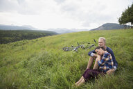 Affectionate senior couple relaxing near mountain bikes in remote rural field - HEROF03619