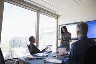 Business people talking in meeting in urban conference room - HEROF03631