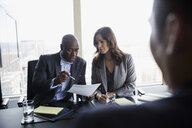 Business people reviewing paperwork in conference room meeting - HEROF03646