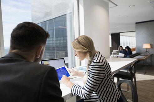 Business people using digital tablet at urban office window - HEROF03652