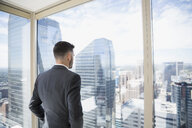 Businessman looking at cityscape view from urban office window - HEROF03667