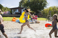 Brother and sisters running and splashing in sunny summer lake - HEROF03703