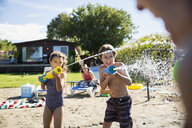 Brother and sister playing with squirt guns at sunny summer beach - HEROF03712