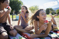 Brother and sisters eating watermelon on sunny summer beach - HEROF03715