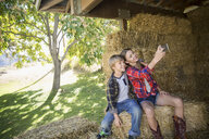 Brother and sister with camera phone taking selfie on hay bale in barn - HEROF03733