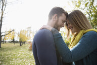 Affectionate couple hugging head to head in autumn park - HEROF03769