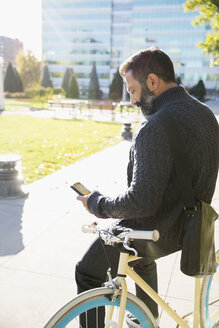 Businessman commuting with bicycle texting with cell phone in sunny urban park - HEROF03841
