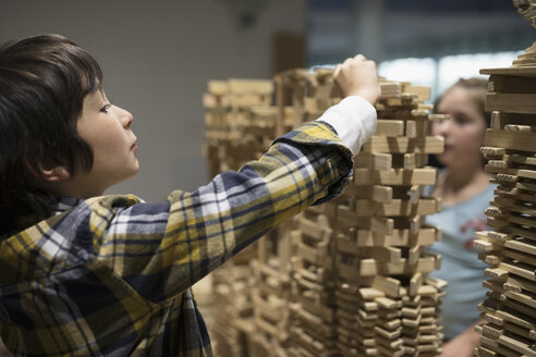 Boy and girl stacking wood pieces in science center - HEROF03850