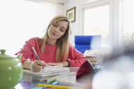 Young woman doodling drawing in notebook at dining table - HEROF03871