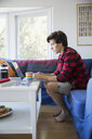 Young man using laptop in living room - HEROF03880