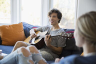 Young couple relaxing playing guitar on living room sofa - HEROF03889