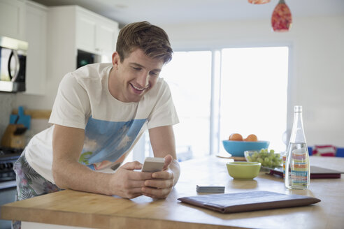 Young man texting with cell phone at kitchen island - HEROF03898