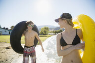 Young couple with inner tubes on sunny summer lake beach - HEROF03907