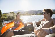 Young couple holding hands drinking water in inflatable rafts on sunny summer lake - HEROF03931