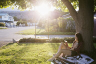 Young woman reading book against tree in summer sunny yard - HEROF03946