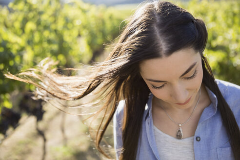 Wind blowing hair of brunette woman looking down in sunny vineyard - HEROF04015