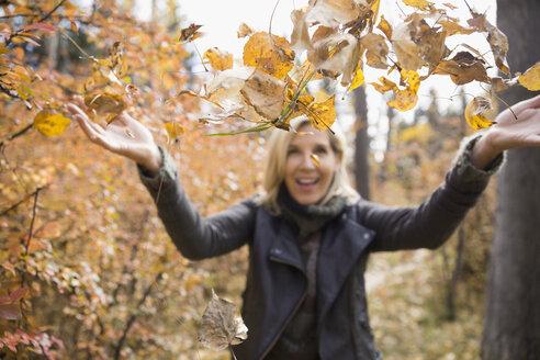 Woman throwing autumn leaves in woods - HEROF04072