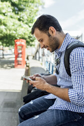UK, London, smiling man using his smartphone on the street - MGOF03901