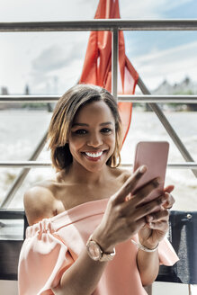 UK, London, portrait of beautiful smiling woman holding cell phone while traveling by boat on the River Thames - MGOF03907