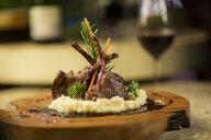 Garnished lamb chop on wooden serving plate - ZEF16120